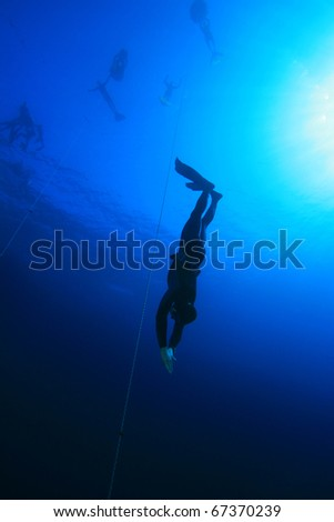 Freediver dives into the depths of the Red Sea in the Blue Hole, Dahab, Egypt - stock photo