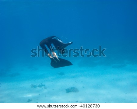 Freediver with monofin makes turn near the Red Sea bottom. - stock photo