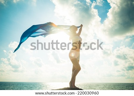 Freedom and beauty concept. Beautiful girl with blue scarf standing on the Rock. Flying. Free. Vacation - stock photo