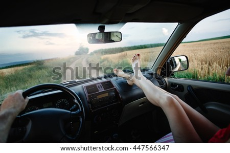 Freedom car travel concept - woman relaxing with feet on dashboard. Sexy woman in the car.