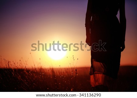 Freedom concept. Beautiful woman enjoying colorful sunset in the field