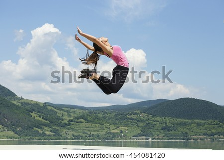Freedom . Girl jumping by the river