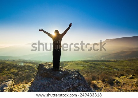 freedom girl with hands up in the mountains against sun - stock photo