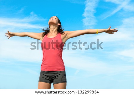 Freedom happy concept. Free woman raising arms to clear blue sky. Beautiful,  joyful and blissful caucasian girl. - stock photo