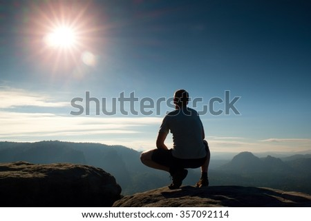 Freedom hiker  sit upper the misty valley and enjoy morning in beautiful nature
