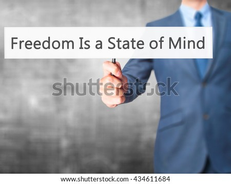 Freedom Is a State of Mind - Businessman hand holding sign. Business, technology, internet concept. Stock Photo - stock photo