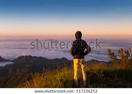 freedom man on top of mountain with flowing mist and beautiful sunset