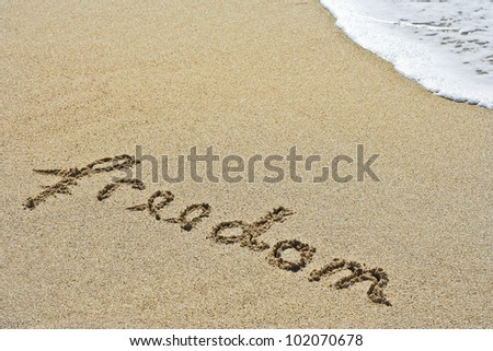 Freedom message written in the sand blue ocean in the background - stock photo