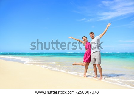 Freedom on beach vacation - happy carefree winning couple with arms up showing happiness and fun on paradise beach with perfect pristine turquoise water in sunny tropical getaway - stock photo
