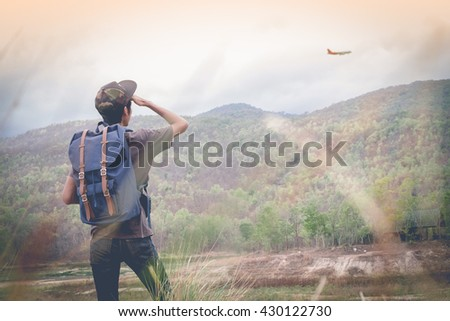 Freedom traveler man standing and look at a plane enjoying a beautiful nature. Image with vintage filter - stock photo