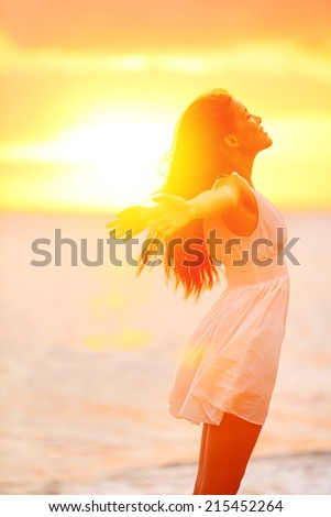 Freedom woman enjoying feeling happy free at beach at sunset. Beautiful serene relaxing woman in pure happiness and elated enjoyment with arms raised outstretched up. Asian Caucasian female model. - stock photo
