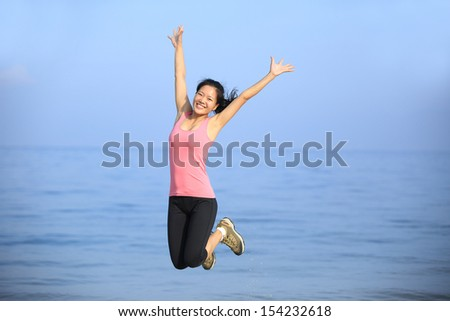freedom woman jumping at beach - stock photo