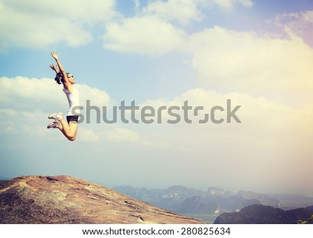 freedom young asian woman jumping on mountain peak rock  - stock photo