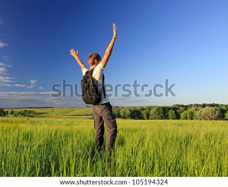 Freedom young man with a backpack relax on a nature field - stock photo