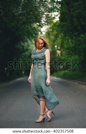 Freedom Young Woman in Grey Dress Standing or Dancing on the Road Alone in Summer Evening. Femininity Concept.