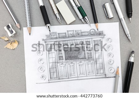 freehand sketch design of wall unit with pens and pencils on desk - stock photo