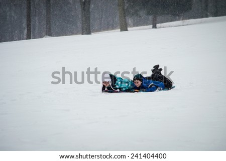 FREEHOLD, NEW JERSEY-FEBRUARY 14- Kids enjoy sledding in Monmouth Battlefield State Park on February 14 2014 in Freehold New Jersey. - stock photo