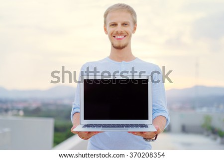 Freelance and technology. Outdoors portrait of handsome young man holding computer, showing screen with copy space. Focus on laptop. - stock photo