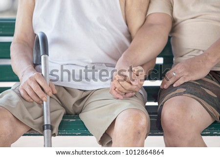 Freelance  Asian Nurse or Son holding hands with senior man 80 years sitting on the chair in garden.A son take care his father who has alzheimer's disease. Father very happy when go to park.
