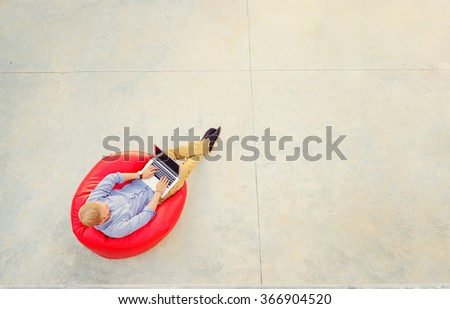 Freelance concept. Top view of young man working on laptop sitting on the red bean bag. - stock photo