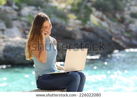 Freelance woman working in vacation on the phone on the beach with the sea in the background  - stock photo
