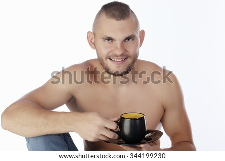 Freelance young guy with a naked torso in jeans sitting on the table, working on the laptop on white background studio