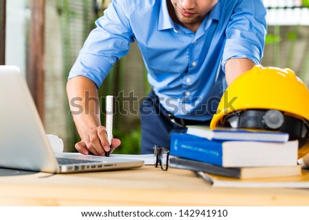 Freelancer - Architect working at home on a design or draft, on his desk are books, a laptop and a helmet or hard hat - stock photo