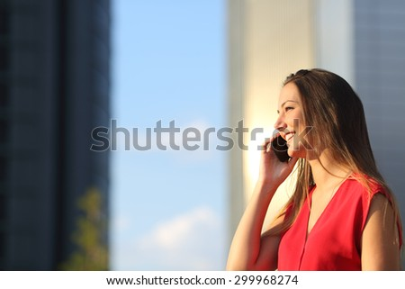 Freelancer business woman talking on the mobile phone with office buildings in the background - stock photo