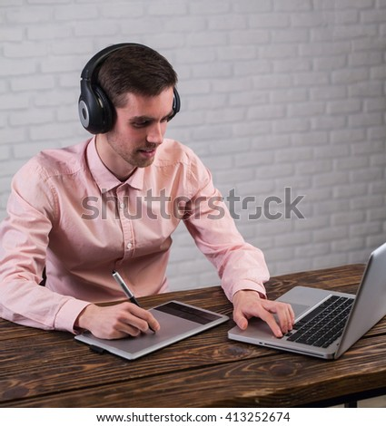Freelancer male in light  shirt is sitting on white brike wall background and working