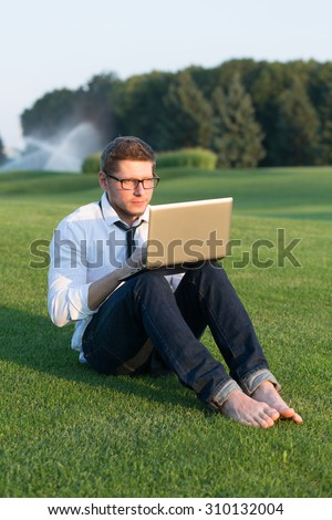 Freelancer man with laptop at summer park on bright day. Man in casual working on his notebook and sitting on the grass. - stock photo