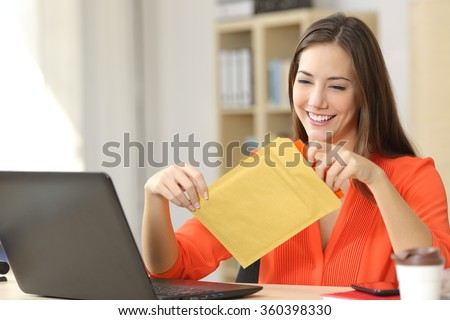 Freelancer opening a padded envelope in an office or home - stock photo