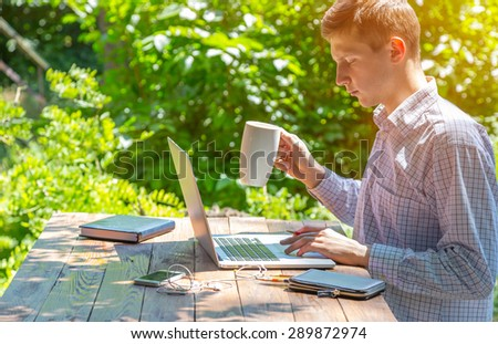 Freelancer working in park. Man sitting at rough country wooden desk working on computer drinking coffee business dress code electronic gadgets notepad around green forest sunbeams on background. - stock photo