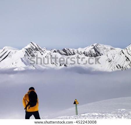 Freerider on off-piste slope in mist and warning sing. Caucasus Mountains, Georgia, ski resort Gudauri. - stock photo