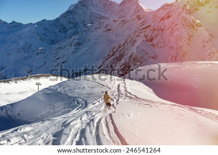 Freerider snowboarder moving down on the background of beautiful Caucasian mountains on Elbrus. Beautiful side effect sunbeam - stock photo