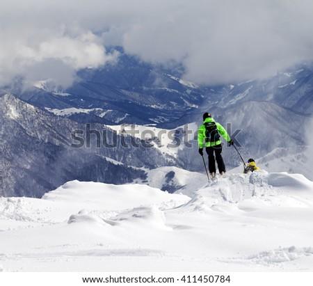 Freeriders on off-piste slope and mountains in mist. Caucasus Mountains, Georgia, ski resort Gudauri. - stock photo