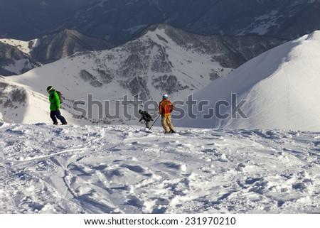 Freeriders on off-piste slope in sun evening. Caucasus Mountains, Georgia. Ski resort Gudauri. - stock photo