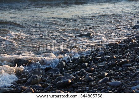 Freestream tranquil waves on the pebble beach  - stock photo
