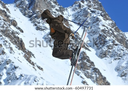 freestyle ski jumper in brown suit with snow covered mountains in the background