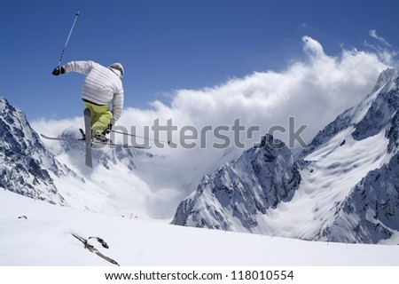 Freestyle ski jumper with crossed skis in high mountains - stock photo