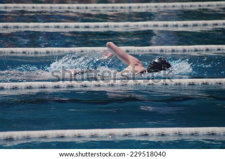 Freestyle swimmer in the outdoor swimming pool - stock photo