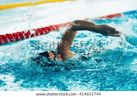 Freestyle swimming competitor in action - stock photo