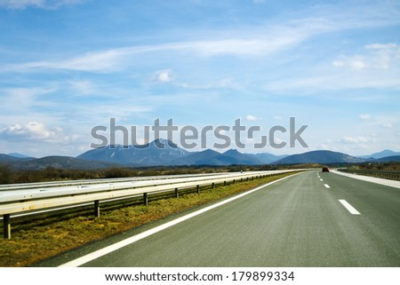 Freeway by the distant mountains - stock photo