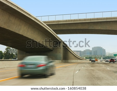 Freeway interchange, overpass, and fast cars.Concrete elevated roadway merging with multiple lane freeway.Fast cars, blurred motion.Fenced overpass. Blue sky, tall buildings in background.  - stock photo
