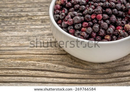 freeze dried elderberries in white, ceramic bowl against grained wood - stock photo