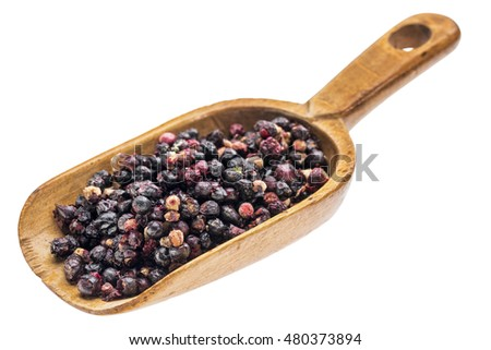 freeze dried elderberries on a rustic wooden scoop, isolated on white