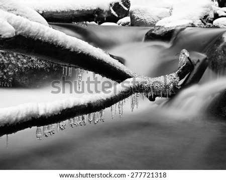 Freeze inter view to icicles on twigs and icy boulders above rapid stream. Reflections of head lamp in icicles. Black and white photo - stock photo