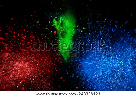 Freeze motion of colorful powder exploding, isolated on black, dark background. Abstract design of dust cloud. Particles explosion, screen saver wallpaper with copy space. Vivid yellow green red ash