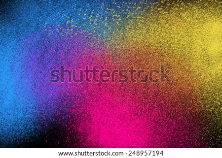 Freeze motion of colorful powder exploding isolated on dark black background. Abstract explosion design of yellow blue magenta, purple, violet dust. Particles cloud wallpaper. - stock photo