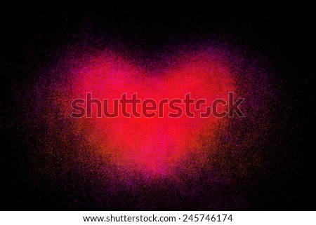 Freeze motion of heart shaped red powder isolated on black, dark background. Abstract design of dust cloud. Particles explosion screen saver, wallpaper with copy space. Love, passion, feelings concept - stock photo