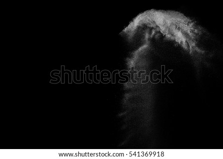 Freeze motion of white particles on black background. Powder explosion. Abstract dust overlay texture.